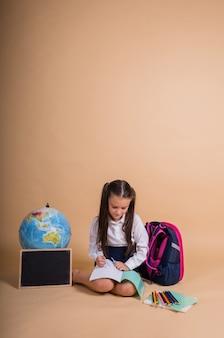 Une écolière en uniforme est assise avec des fournitures scolaires écrivant dans un cahier sur fond beige avec une place pour le texte
