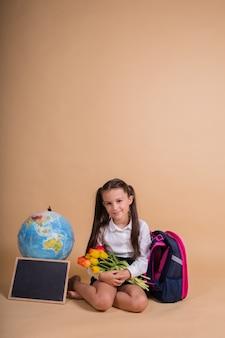 Une écolière en uniforme est assise avec des fournitures scolaires sur fond beige avec une place pour le texte