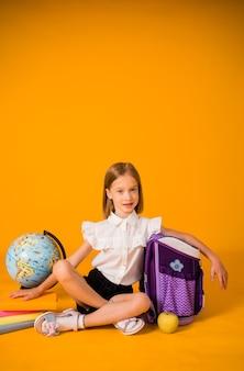 Une écolière en uniforme est assise par terre avec des fournitures scolaires sur fond jaune avec une place pour le texte