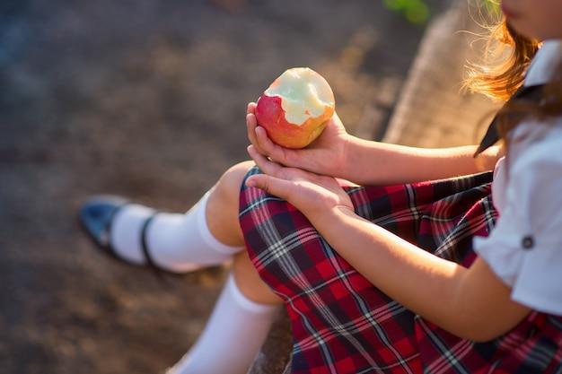 Écolière en uniforme mange une pomme dans le parc.