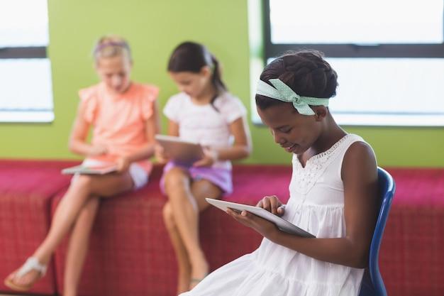 Écolière, utilisation, tablette numérique, dans, bibliothèque