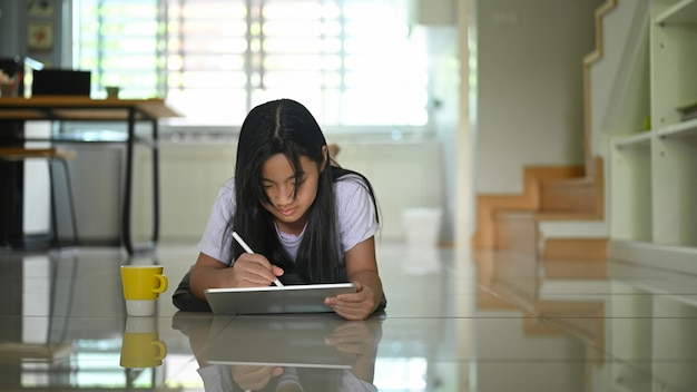 Une écolière utilise une tablette informatique et un stylet dans le salon