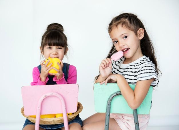 Écolières d'âge élémentaire assis sur une chaise sur le fond blanc