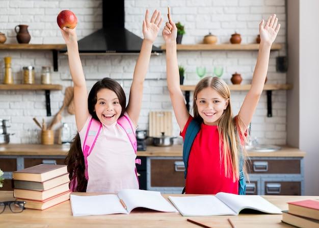 Écolières, à, mains haut, debout, dans, cuisine