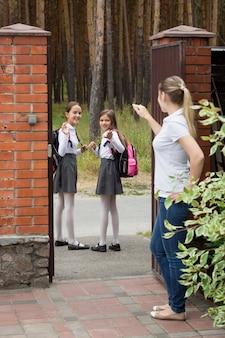 Des écolières souriantes vont à l'école et saluent leur mère