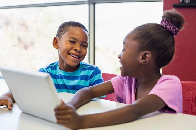 Les écoliers à l'aide d'une tablette numérique en classe