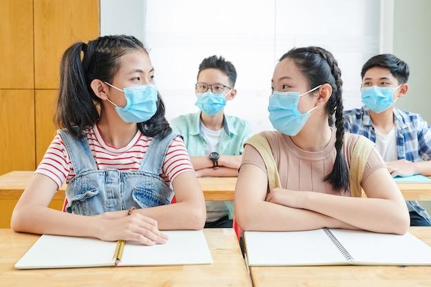 Des écoliers asiatiques assis en classe avec des masques médicaux sur le visage en raison de la pandémie de coronavirus