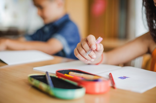 Écoliers assis au bureau avec des cahiers