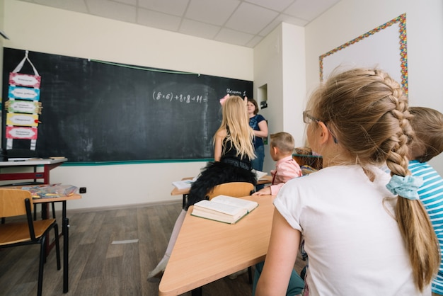 Écoliers assis à la leçon étudiant