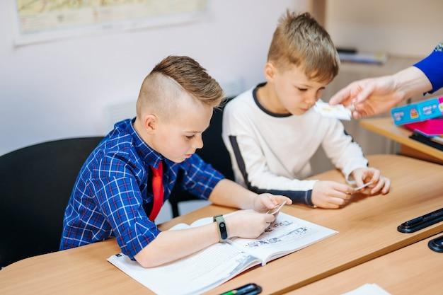 Des écoliers concentrés assis au bureau et écrivant dans un cahier avec un camarade de classe assis derrière.