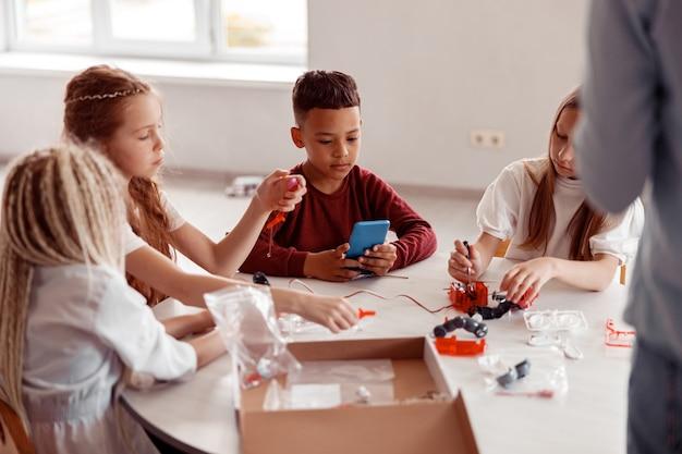 Les écoliers construisent un modèle avec les détails du constructeur à l'école