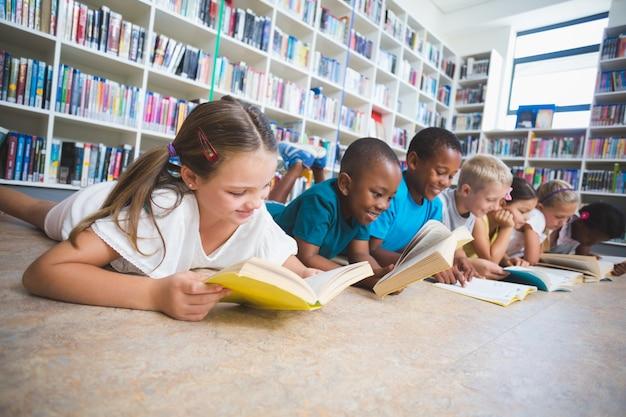 Écoliers, coucher plancher, livre lecture, dans, bibliothèque