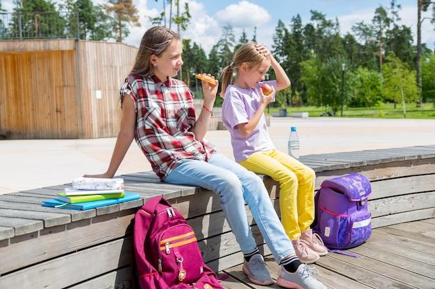 Les écoliers déjeunent ensemble à l'extérieur du bâtiment. filles dans le jardin partageant le déjeuner