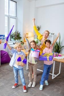 Des écoliers élégants. écoliers élégants debout près de l'enseignant avec leurs boîtes à cadeaux après la leçon d'art