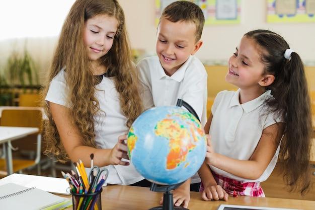 Les écoliers étudient le monde debout dans la salle de classe