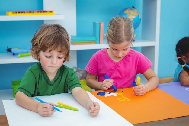 Des écoliers faisant de l'art à leur bureau