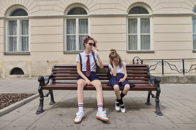 Des écoliers fatigués assis sur un banc. adolescent de deux filles sœurs et élève du primaire