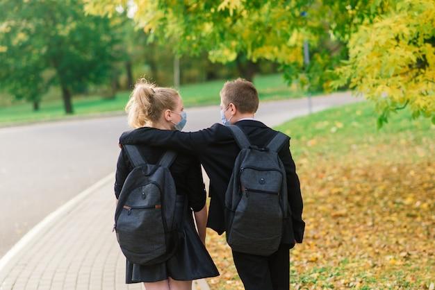 Des écoliers, un garçon et une fille portant des masques médicaux marchent dans le parc de la ville.