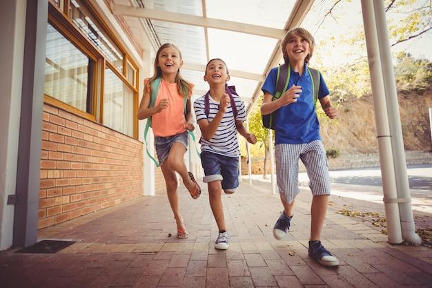 Écoliers heureux courir dans le couloir