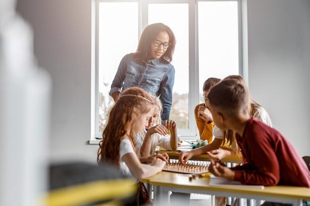 Écoliers heureux utilisant le géoplan en classe ensemble