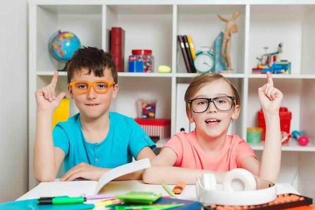 Écoliers intelligents apprenant ensemble en classe.