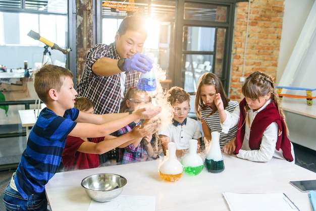 Des écoliers intéressés étudient les réactions chimiques d'échange sur l'exemple des liquides colorés dans des flacons en verre.