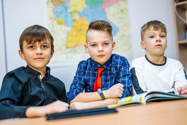 Les écoliers sur la leçon à l'école primaire. garçons regardant la caméra. mise au point sélective.