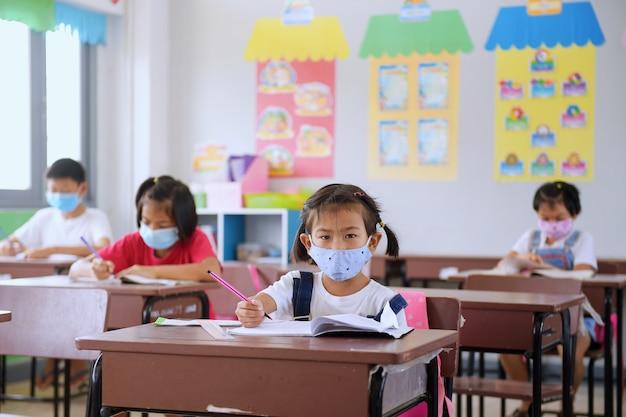 Écoliers avec masque de protection contre le virus de la grippe au cours en classe