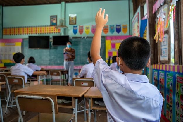 Les écoliers portant un masque facial, groupe d'écoliers avec enseignant assis dans la salle de classe et levant les mains,