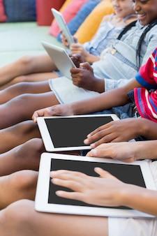 Écoliers, séance, sur, sofa, et, utilisation, tablette numérique, dans, bibliothèque