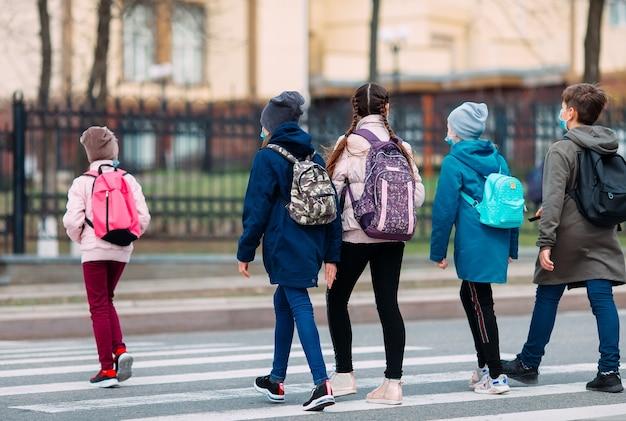 Les écoliers traversent la route avec des masques médicaux. les enfants vont à l'école.