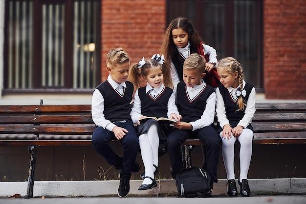 Des écoliers en uniforme assis à l'extérieur sur le banc avec un bloc-notes.