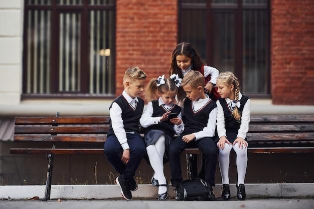 Des écoliers en uniforme assis à l'extérieur sur le banc avec un smartphone.