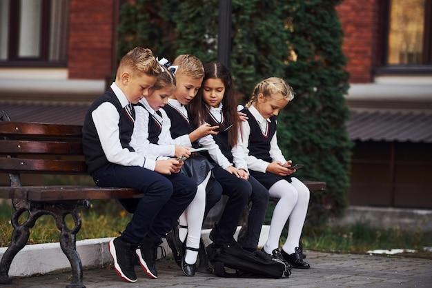 Des écoliers en uniforme assis à l'extérieur sur le banc avec des smartphones.