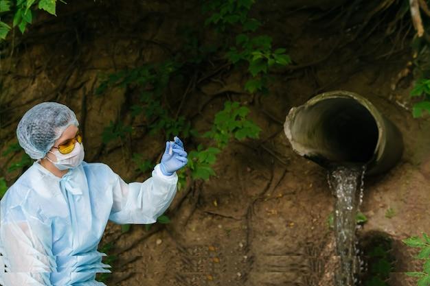 L'écologiste ou l'épidémiologiste évalue le contenu du tube à essai contre les égouts sortant du sol