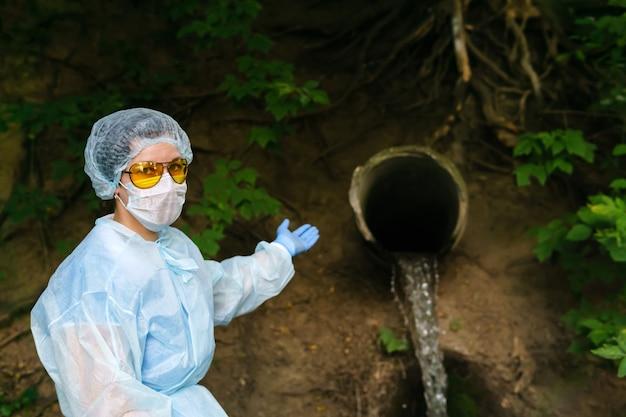 Une écologiste ou une épidémiologiste portant une blouse de protection et un masque indiquent un égout qui sort