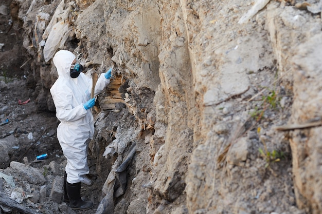 Écologiste en tenue de protection examinant les échantillons de roches dans la nature