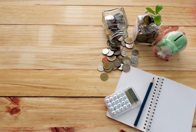 Économies d'argent, pièces de monnaie, piggy, calculatrice, note, crayon sur le dessus pour l'espace