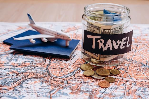 Économies d'argent de vacances dans un bocal en verre avec texte de voyage