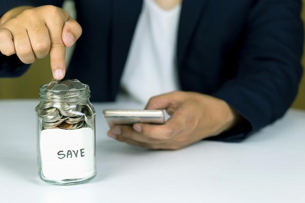 Économies déposer des pièces dans une bouteille en verre clair, espace de copie.