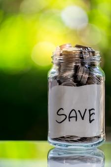 Économies, déposez des pièces dans une bouteille en verre clair, sur un plancher en bois avec bokeh au dos