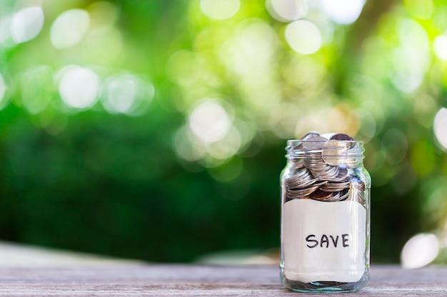 Économies, déposez des pièces dans une bouteille en verre transparent, sur un plancher en bois avec bokeh au dos