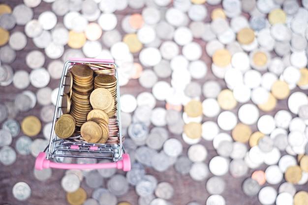 Économiser de l'argent concept avec pièce dans le panier sur fond de pièces flou