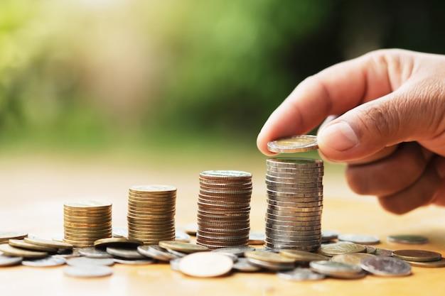 Économiser de l'argent main mettre des pièces sur la pile sur la table avec le soleil. concept finance et comptabilité