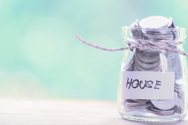 Économiser de l'argent pour la maison, pièces de monnaie dans un bocal en verre avec devis maison sur table en bois