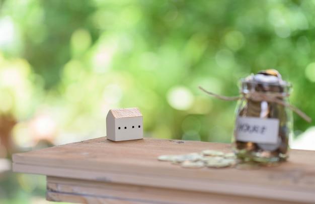 Économiser de l'argent pour la maison, pièces en pot de verre avec devis maison sur table en bois