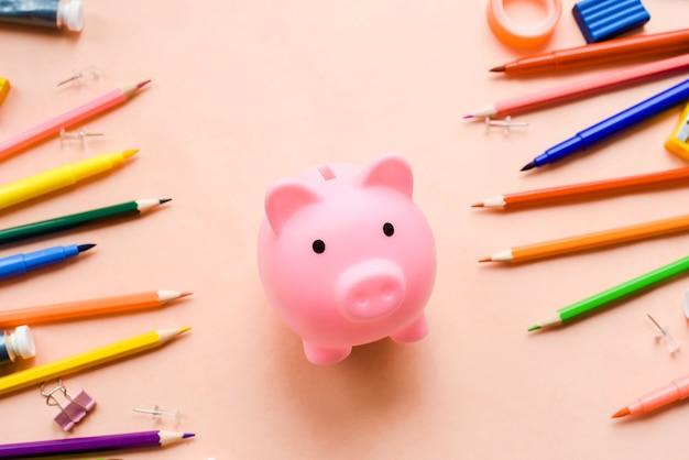 Économiser pour l'éducation ou le concept de retour à l'école, tirelire et marqueur coloré, crayon et stylo