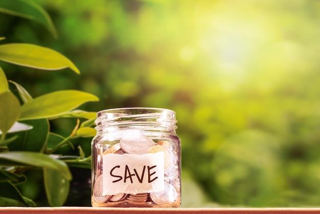 Économisez de l'argent, des pièces de monnaie dans un bocal en verre pour un concept financier économique