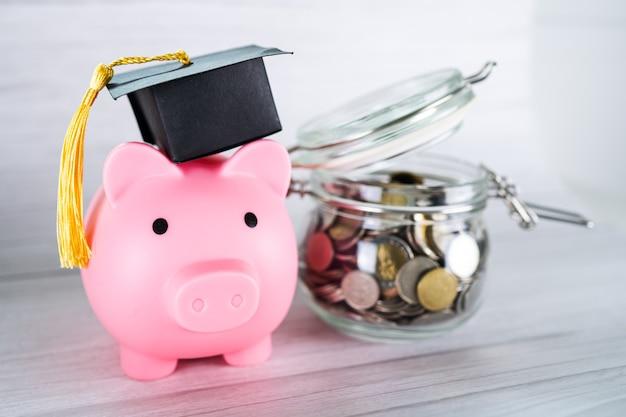 Économisez des pièces d'argent dans un pot d'herbe avec tirelire et chapeau de graduation