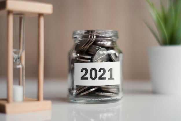 Économisez pour un objectif et un rêve en 2021. pot en verre avec des pièces de monnaie.